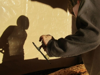 A young carver uses a D-adze to help shape our forthcoming welcoming pole. (Quentin Harris)